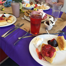 A cloth-covered table with plates of cookies and waffles with strawberries