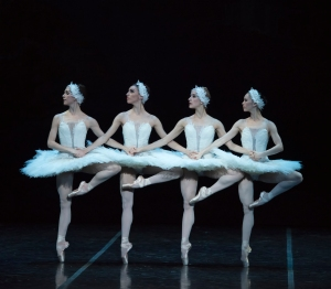 4 dancers in white, swan-like tutus, all balanced on one leg