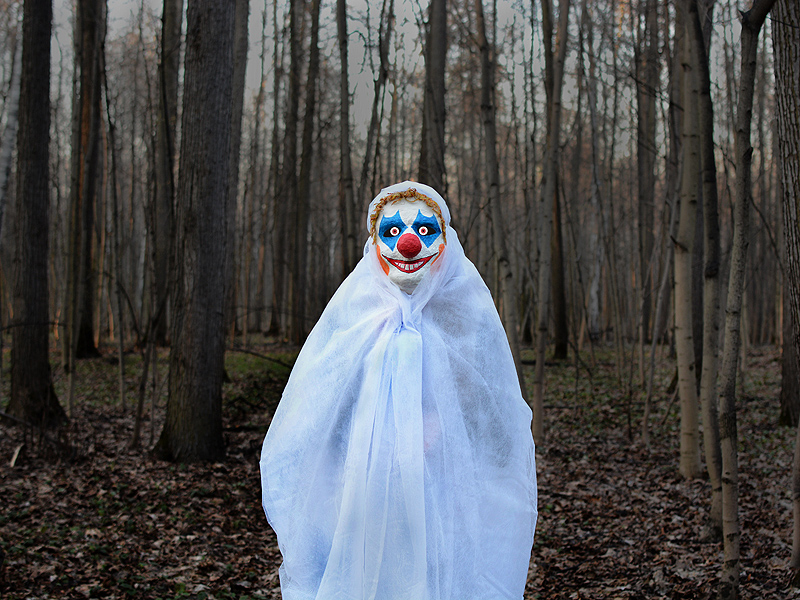 evil clown in a dark forest in a white veil