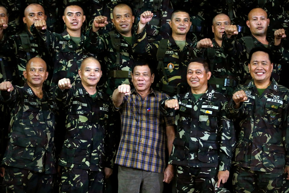 """Philippine President Rodrigo Duterte makes a """"fist bump"""", his May presidential elections campaign gesture, with soldiers during a visit at Capinpin military camp in Tanay"""