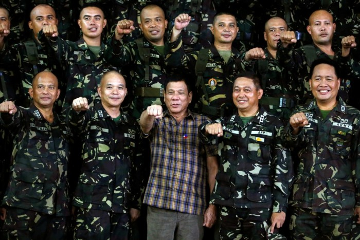 "Philippine President Rodrigo Duterte makes a ""fist bump"", his May presidential elections campaign gesture, with soldiers during a visit at Capinpin military camp in Tanay"