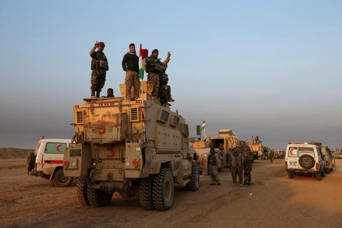 Peshmerga forces stand on a military vehicle in the town of Bashiqa
